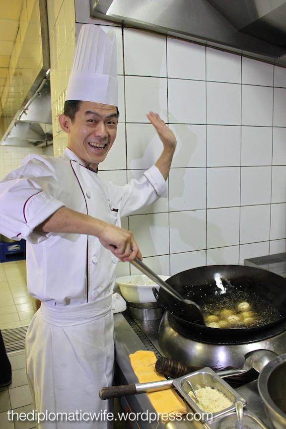 Chef John's jolly pose as he fries the Crispy black and white sesame ball with peanut paste & macadamia nut
